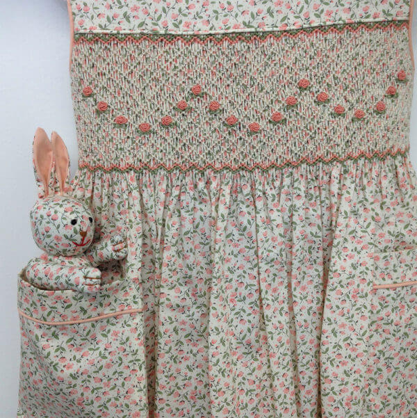 peach petite floral pattern hand smocked dress with peach floral garland embroidery pattern and matching Pocket Pal® bunny in the pocket