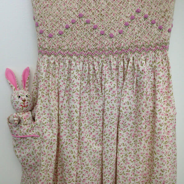 closeup of pink petite floral pattern hand smocked dress with pink floral garland embroidery pattern and matching Pocket Pal® bunny in the pocket