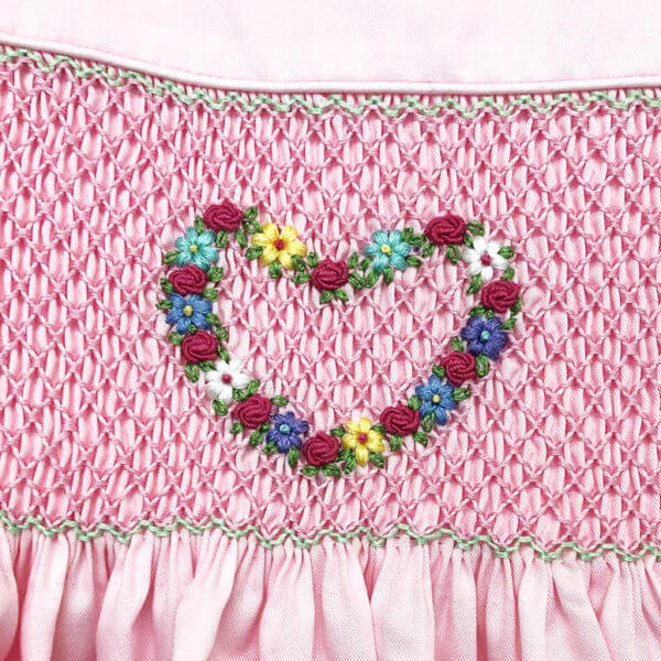 closeup view of floral heart embroidery on pink hand smocked girl's dress