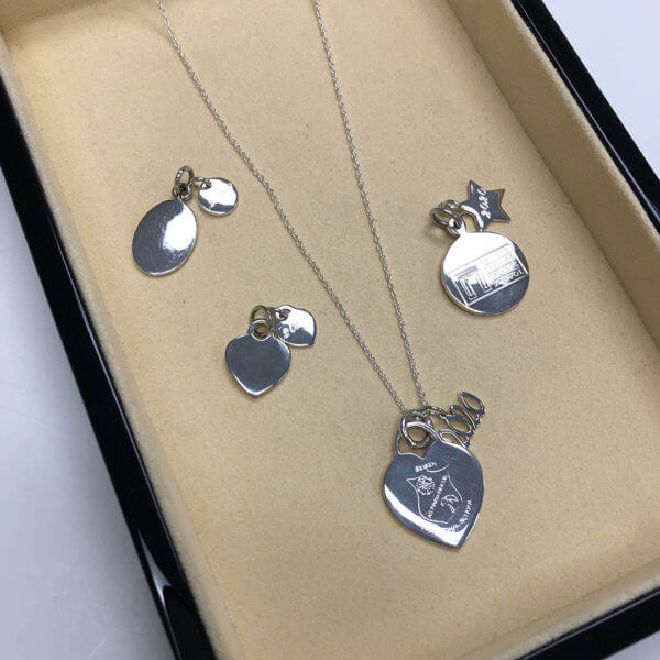 Assortment of sterling silver pendants paired with grad year charms