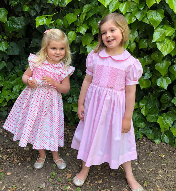Models in hand smocked tiny hearts dress and pink dress with sleeves and Peter Pan collar